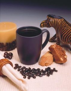 cup of black coffee with biscotti, wooden zebra, and candle