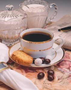 white china cup of black coffee with crystal containers of sugar and cream. Biscotti and chocolate covered espresso beans on saucer.