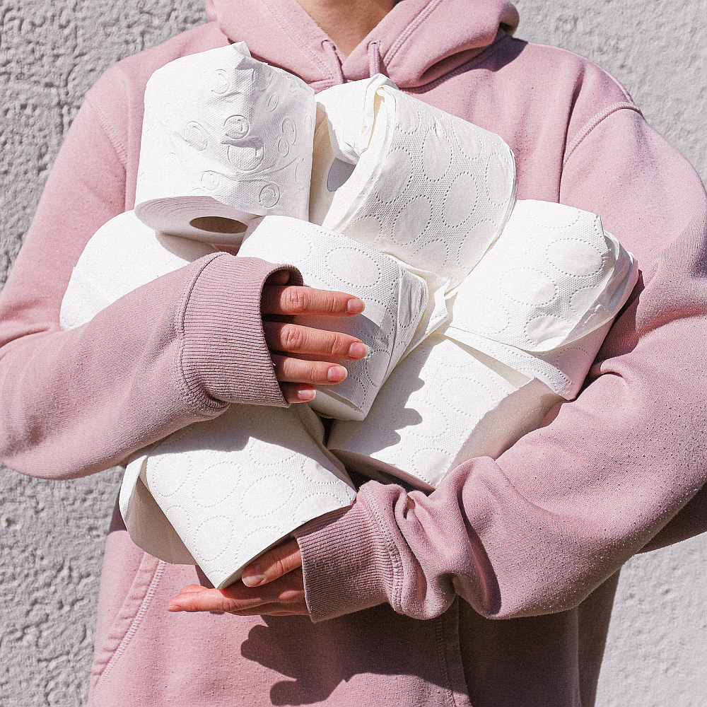 woman-in-pink-long-sleeve-hoodie-carrying-toilet-paper-rolls