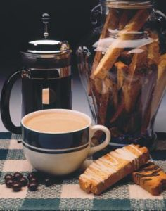 large cup of cappuccino with jar of biscotti and French Press of coffee